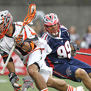 Justin Pennington #14 of the Denver Outlaws runs away from Paul Rabil #99 of the Boston Cannons with the ball during the game at Harvard Stadium on May 10, 2014 in Boston, Massachusetts. (Photo by Elan Kawesch)