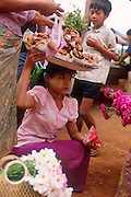 Laden with flowers and doughnut at a village market.<br /> Tenasserim region, burma 2000