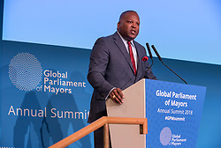 © Licensed to London News Pictures. 22/10/2018. Bristol, UK. Global Parliament of Mayors Annual Summit, 21-23 October 2018, at Bristol City Hall. Picture of STEVE BENJAMIN, Mayor of Colombia, South Carolina, USA, addressing the conference. The Global Parliament of Mayors 2018 is the biggest and most ambitious Annual Summit to date. GPM Bristol 2018 will host up to 100 global mayors for an action-focused summit that addresses some of the biggest challenges facing today's world cities. GPM Bristol 2018's theme, Empowering Cities as Drivers of Change, will focus minds on global governance and the urgent need for the influence, expertise and leadership of cities to be felt as international policy is shaped. GPM Bristol 2018 will provide mayoral delegates with a global network of connections and a space to develop the collective city voice necessary to drive positive change. The programme will engage participants in decision-making, with panels, debate and voting on priority issues including migration and inclusion, urban security and health, and is a unique chance to influence decisions on the most pressing issues of our time. Photo credit: Simon Chapman/LNP