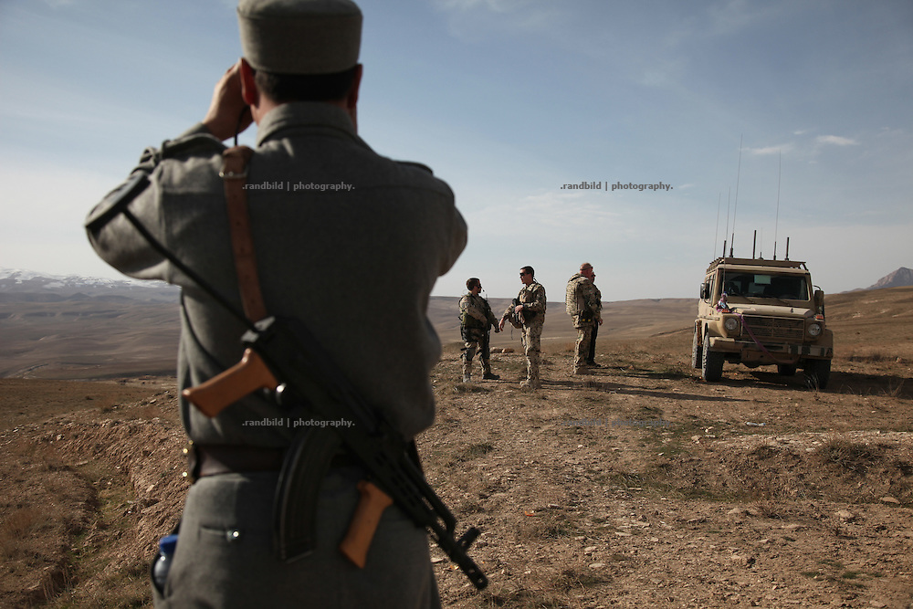 Police officers of the Afghan National Police oberves the surroundings in Marmal mountain range.