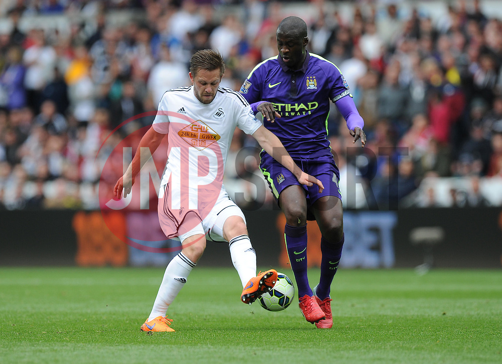 Swansea City's Gylfi Sigurosson battles for the ball with Manchester City's Yaya Toure - Photo mandatory by-line: Alex James/JMP - Mobile: 07966 386802 - 17/05/2015 - SPORT - Football - Swansea - The Liberty stadium - Swansea City v Manchester City - Barclays premier league