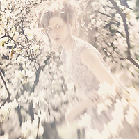A ghostly backlit woman walks amongst sunlit trees in the spring time.