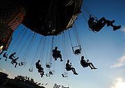 "Guests riding the ""Wave Swinger"" are silhouetted in the late afternoon light while at the Gwinnett County Fair on Tuesday at the Gwinnett County Fairgrounds in Lawrenceville. (Staff Photo: David Welker)"