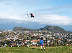 View of boy flying kite and Salisbury Crags and Arthur's Seat hill overlooking Edinburgh, Scotland, United Kingdom