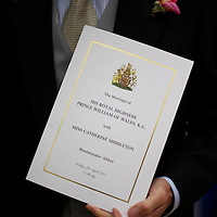 Prince William and Kate Middleton were married at Westminster Abbey with over 1900 guests attending.  A guest clutches the ceremony program as he leaves the media headquarters.