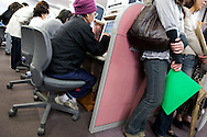 Sitting at computer work stations and standing with folders in hand, people fill in job applications and seek work at the 'Hello Work' employment office, in Toyota city, Japan, on Tuesday 21st April 2009.  In the first 3 months of 2009 the numbers of people seeking work at the 'hello Work' employment office rose 133% compared to the first quarter of 2008. This increase is due to the jobs lost in the industries and companies which serve and supply the Toyota car company and automobile industry, for which Toyota city is famous.