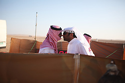 In the waiting area before the falcon races, competitors greet each other in a traditional Gulf manner, touching noses.