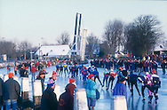 Nederland, Friesland, 19970104..De Elfstedentocht in januari 1997 in Friesland..Schaatsers rijden door de polders.  Mensen staan te kijken naar de schaatsers die voorbij komen. 6000 schaatsers en meer dan een miljoen toeschouwers..Rijen schaatsers passeren een openstaande brug...The Elfstedentocht is a speed skating competition and leisure skating tour in the province of Friesland in the Netherlands..6.000 skaters and over a million spectators were present. The route takes the skaters through eleven cities in Frisia, in the North of Holland. Flag of the provence Friesland. 200 kilometre race along the frozen canals of Friesland..Row of skaters pass an open bridge.