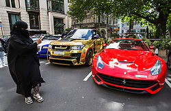 © Licensed to London News Pictures. 27/07/2015. London, UK. A woman wearing a burqa takes photos of a collection of supercars seen outside the Dorchester Hotel in London. Kensington and Chelsea Borough Council have announced plans that will make it a criminal offence to cause excessive noise unnecessarily, which will aim to stop showboating by drivers revving their engines, or super-fast accelerating. Photo credit : James Gourley/LNP