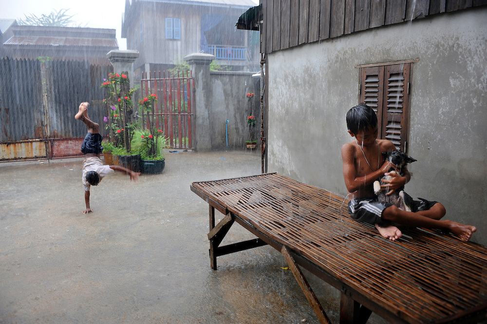 Boys playing duing a downpour in Phnom Penh, Cambodia 23/09/2008