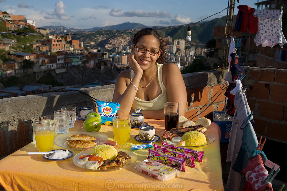 Katherine Navas, a high school student, on the roof of her family's home in a barrio in Caracas, Venezuela with her typical day's worth of food.  (From the book What I Eat: Around the World in 80 Diets.) The caloric value of her typical day's worth of food in the month of November was 4,000 kcals. She is 18 years of age; 5 feet, 7 inches tall; and 157 pounds.  Unlike housing in most of the developed world, the higher the house, the cheaper the rent in the dangerous Caracas barrios. Those living at the top of the steep hillside have to travel the farthest to reach services, shops, and the main street, a trip normally made only in the daylight hours. MODEL RELEASED