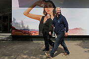 Two blokish men walk past a billboard ad featuring the face of a model advertising a perfume outside the retailer Debenhams on Oxford Street, on 16th April 2018, in London, England.