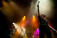 Singer holding microphone to the crowd with colourful backlighting and smoke effects