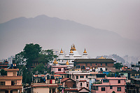Buildings, temple spires, and the mountains beyond in Kathmandu.