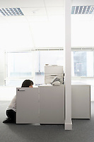 Female office worker kneeling in front of open cabinet in office side view