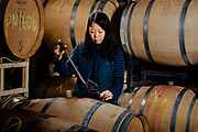Stephanie Pao winemaker for Foris Vineyards in the Illinois Valley, sampling wine from the barrel.