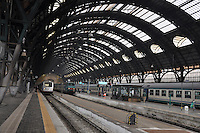 Milan, Italy. Train station - domed glass and metal ceiling with platforms and trains.