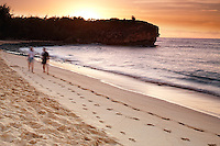 Shipwreck beach in Po'ipu on the island of Kauai, Hawaii. A couple on vacation walks this beautiful beach at dawn enjoying the soft white sand.