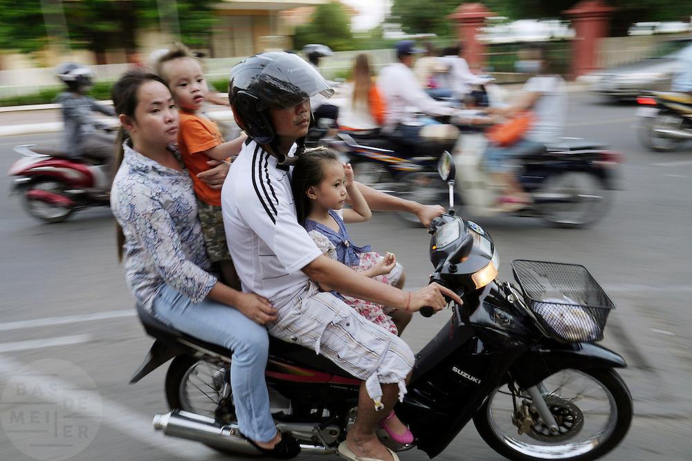 Een gezin rijdt op een brommer door het centrum van Phnom Penh