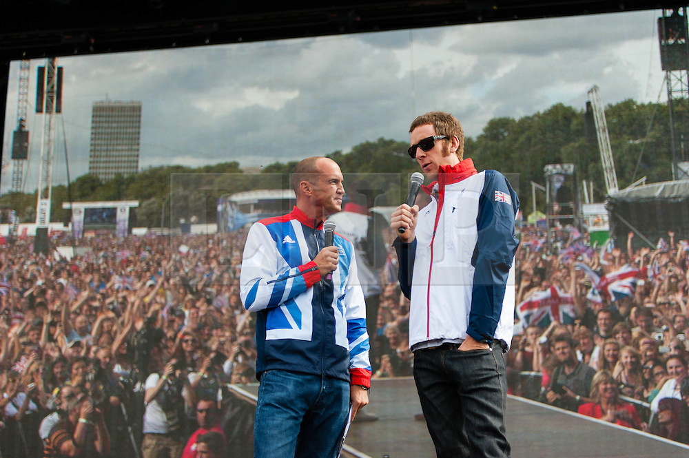 © Licensed to London News Pictures. 04/08/2012. London, UK. Bradley Wiggins, Team GB Olympic Cyclist, being interviewed by Johnny Vaughan on stage at BT London Live, Hyde Park.   The crowds are displayed on a video screen behind Bradley.  Bradley Marc Wiggins, CBE (born 28 April 1980) is a British professional track and road racing cyclist, riding for the UCI ProTeam Team Sky. Wiggins began his career on the track, but has made the transition to road cycling, becoming one of the few cyclists to gain success in both disciplines. He won the 2012 Tour de France, becoming the first British winner in its 99-year history, and has achieved the historic double of Tour de France crown and Olympic gold where he won the Time Trial by a huge 42 second margin in time trial over 27.3 mile south-west London course. He is now Britain's most decorated Olympian, overtaking Steve Redgrave.  BT London Live is series of events across London that combe multiple state-of-the-art screens and concert quality sound systems to show all of the London 2012 events.   Photo credit : Richard Isaac/LNP