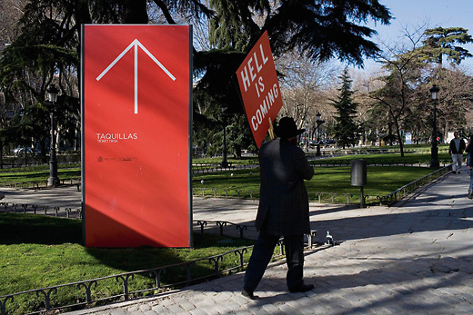 A man walks past The Prado art gallery in Madrid, Spain, holding a sign