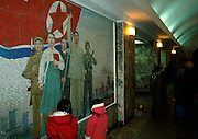 Pyongyang, North Korea. <br />Winter in North Korea Pyongyang underground propoganda mural catches the eye of two small girls while their parents talk while waiting for the train. <br /><br />Picture Credit: Dermot Tatlow