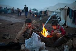 Syrian children warm themselves in front a tent in Atmah's refugee camp. Idlib province, Syria. Situated along the Turkish border Atmah's refugee camp is considered the biggest refugee camp inside Syria's territory with an estimated number of 13,000 refugees and growing by the day. Is the biggest in an area with another two camps.,000 refugees and growing by the day. Is the biggest in an area with another two camps, Syria, February 4, 2013. Photo by Daniel Leal-Olivas / i-Images.