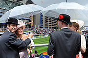© licensed to London News Pictures. ASCOT, UK.  16/06/11. Couples shelter from a rain shower. Ladies Day at Royal Ascot 16 June 2011. Royal Ascot has established itself as a national institution and the centrepiece of the British social calendar as well as being a stage for the best racehorses in the world. Mandatory Credit Stephen Simpson/LNP