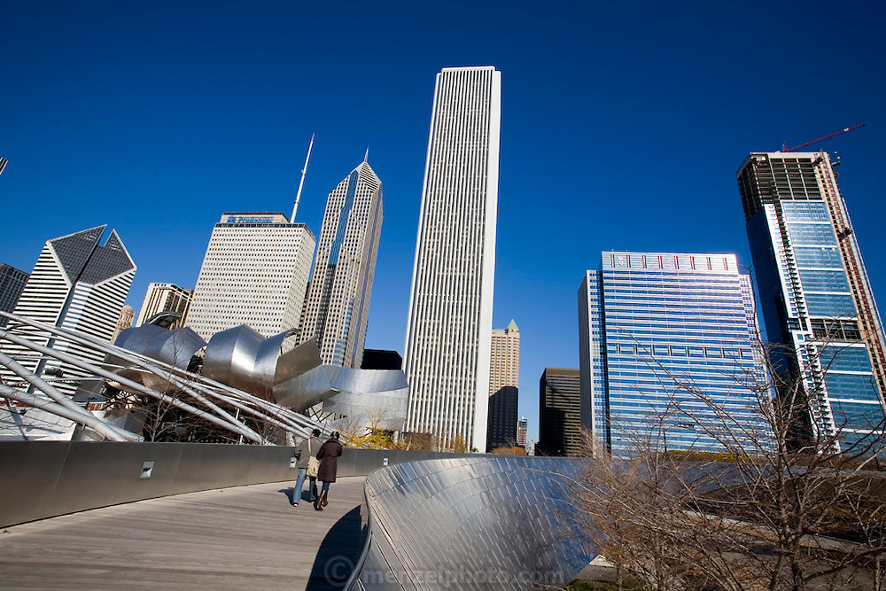 Pedestrians on the Frank Gehry-designed BP Bridge that connects Chicago's Millennium Park with Daley Bicentennial Plaza. To the left, the Jay Pritzker Pavilion, also designed by Gehry, Chicago, Il. USA.