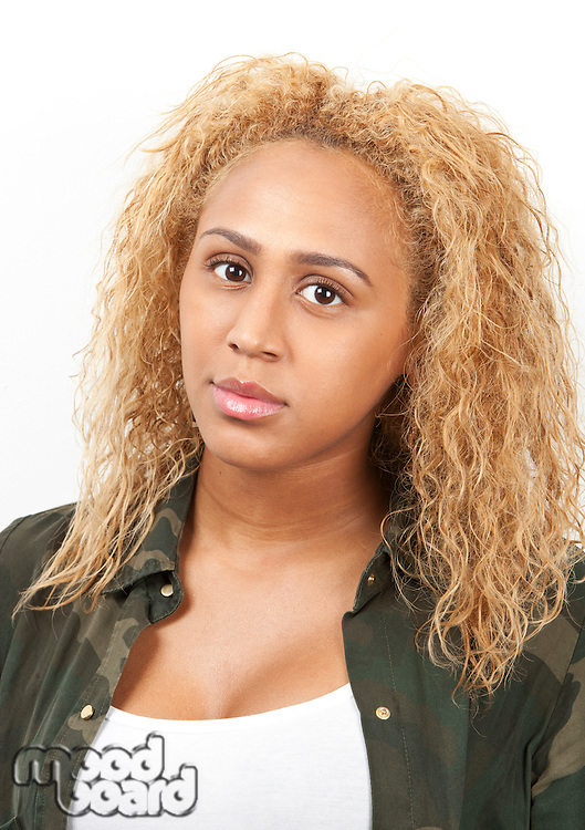 Portrait of young mixed race woman with blond curly hair against white background