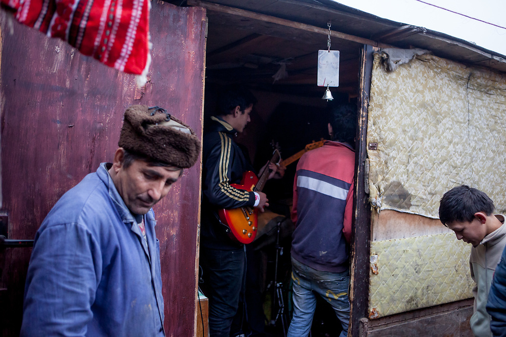 A man stands outside a hut wear a band is playing in the Roma settlement located in 'Budulovska Street' in Moldava nad Bodvou (2012). The city has roughly 11200 inhabitants, about 1980 (18%) of them have Roma ethnicity and around 800 are living at the segregated settlement 'Budulovska Street' (2014).