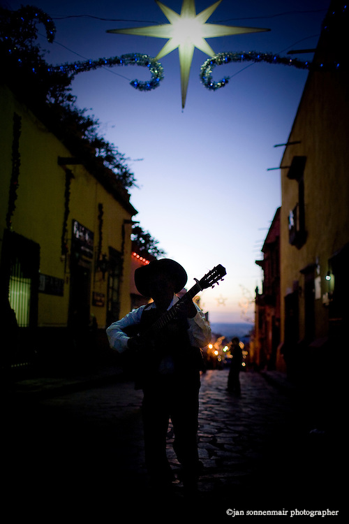 A mariache walks down Calle Umaran, a street leading to center of town in San Miguel de Allende, Mexico..Christmas decorations are up as it is Christmas eve.