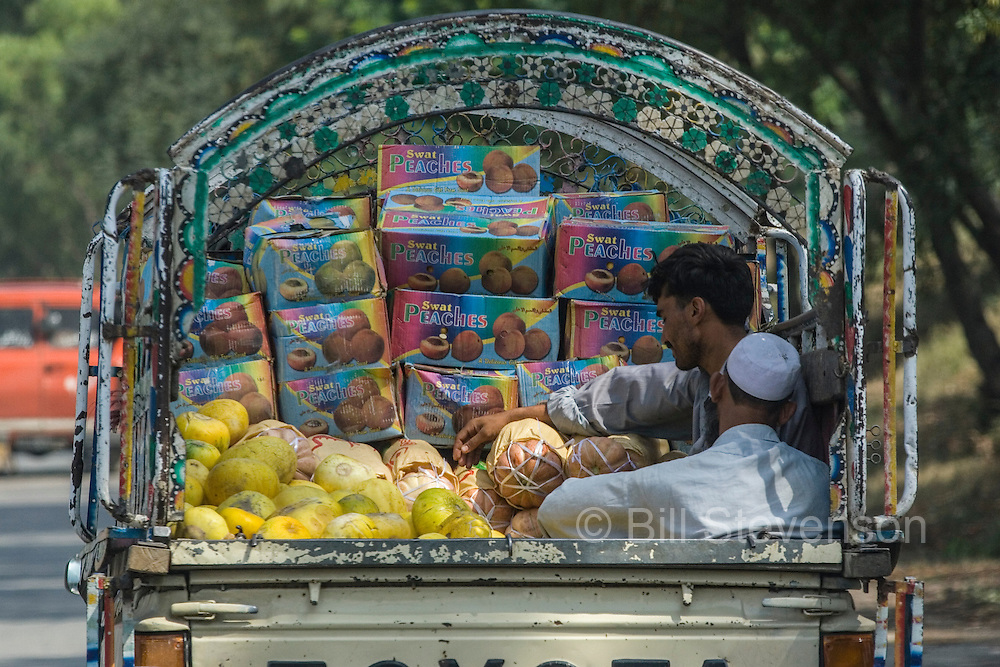 Two Pakistani men traveling in the back of a fruit delivery truck in Islamabad in Pakistan