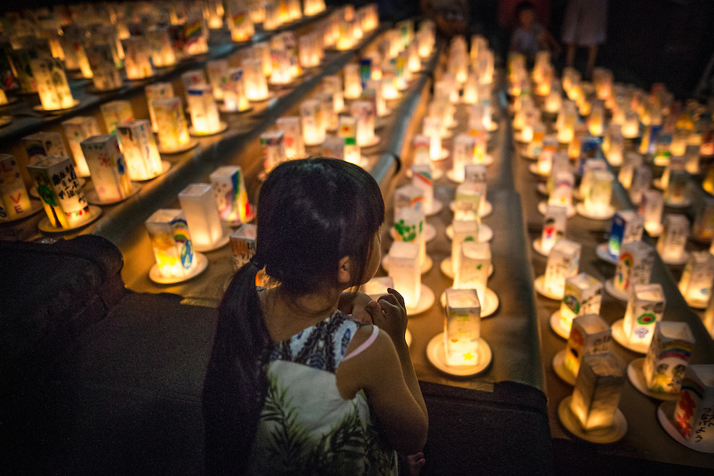 NAGASAKI, JAPAN - AUGUST 8 : A young girl look at candle-lit paper lanterns with written message at Nagasaki Peace Park on the eve ahead of the 71st anniversary activities, commemorating the atomic bombing of Nagasaki on August 8, 2016 in Nagasaki, southern Japan. On August 9, 1945, during World War II, the United States dropped the second Atomic bomb, a plutonium implosion-type bomb on Nagasaki city, killing an estimated 40,000 people which ended the World War II. (Photo by Richard Atrero de Guzman/NURPhoto)