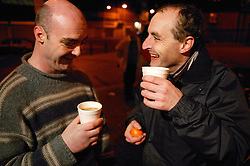 Men enjoying hot drinks from a mobile soup kitchen in Nottingham,