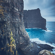 Seabirds swirl around the mighty cliffs of Vágar, Faroe Islands