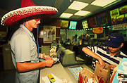Tourist wearing sombrero buying a meal at Mc Donalds Ibiza 1990's