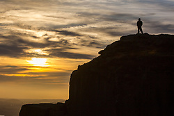 © Licensed to London News Pictures. 13/03/2017. Ilkley UK. A walker stands on top of the Cow & Calf rocks 1,319ft above sea level at sunrise this morning in Yorkshire. Photo credit: Andrew McCaren/LNP