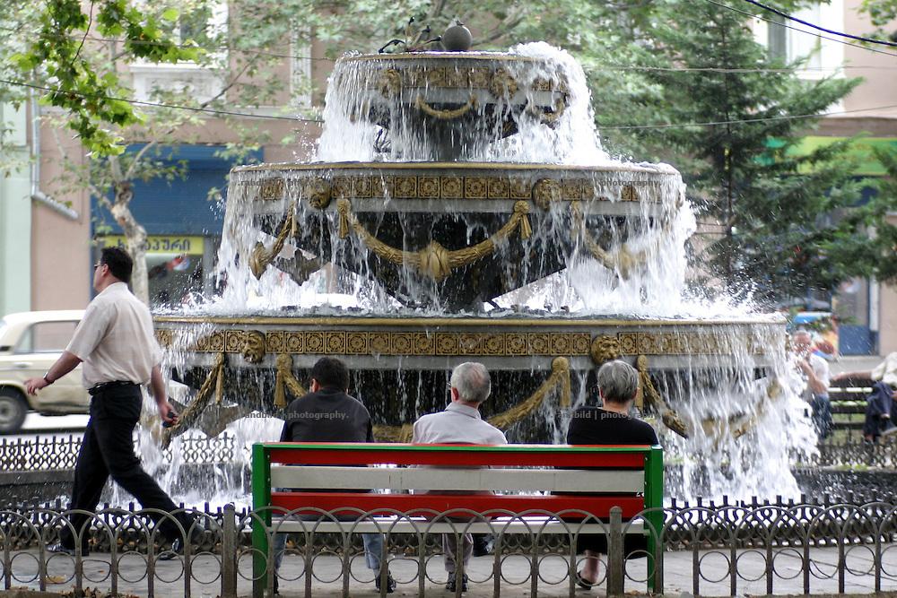Vor einem Brunnen am zentralen Freiheitsplatz in der georgischen Hauptstadt Tiflis sitzen Maenner auf einer Parkank. A fontaine on Tbilissis central Freedom Square, Georgia.
