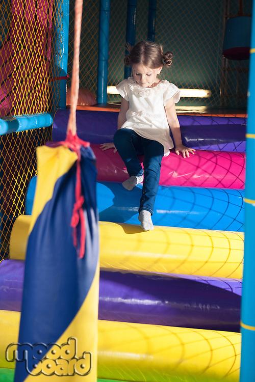Young girl climbing down play gym