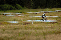 JEROME A. POLLOS/Press..Speeding along the hillside at Schweitzer Mountain, a downhill biker heads toward the exit gate during warm-ups for the Norba Nationals in Sandpoint on Friday.