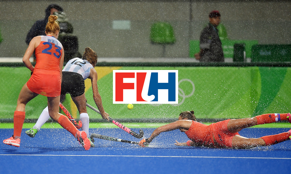 TOPSHOT - Netherland's Maartje Paumen (R) falls on the pitch as she vies for the ball with Argentina's Delfina Merino during the women's quarterfinal field hockey Netherlands vs Argentina match of the Rio 2016 Olympics Games at the Olympic Hockey Centre in Rio de Janeiro on August 15, 2016. / AFP / MANAN VATSYAYANA        (Photo credit should read MANAN VATSYAYANA/AFP/Getty Images)