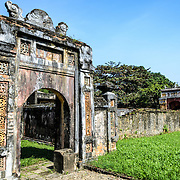 A badly weathered stone gate at the Imperial City in Hue, Vietnam. A self-enclosed and fortified palace, the complex includes the Purple Forbidden City, which was the inner sanctum of the imperial household, as well as temples, courtyards, gardens, and other buildings. Much of the Imperial City was damaged or destroyed during the Vietnam War. It is now designated as a UNESCO World Heritage site.