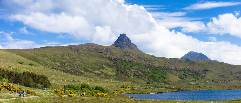 Tourists cycling by loch and Stac Pollaidh - Stack Polly - in glacier mountain range in the North West Highlands Geopark in Coigach region of Scottish Highlands
