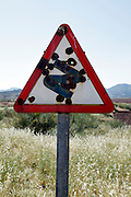 rusty road traffic sign with bullet holes