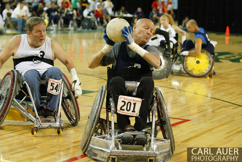 July 7th, 2006: Anchorage, AK - David Nau takes a hard pass as Gustave Sorenson (3) speeds in on defense as White defeated Blue in the gold medal game of Quad Rugby at the 26th National Veterans Wheelchair Games.