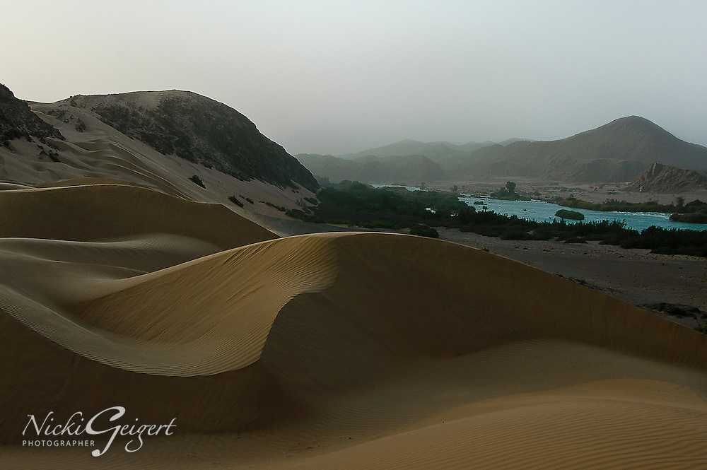 Sand dunes by a flowing river in Namibia, Africa. Fine art photography prints. Nature photography wall art of exotic locations, landscape art.