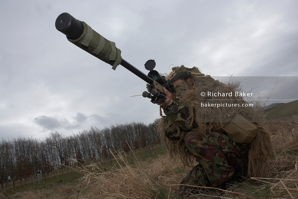 Kneeling in undergrowth, a camouflaged British infantry soldier is seen looking down the telescopic sight of the new British-made Long Range L115A3 sniper rifle on Salisbury Plain, Warminster, England. Sniping means concealment, observation and assassination, a strategy the British are using more against the Taliban in Afghanistan. Swiss Lapua .338 inch rounds (8.59mm) travel at sub-sonic speeds of 936 metres/sec, finding its target accurately up to 1,100 metres. The rifle weighs 6.8kg with telescopic image-intensified scopes to 25x life size vision, made by Schmidt & Bender. Front-mounted 'suppressor' minimises the signature normally compromising snipers' position. At £23,000 each, a £4 million contract has been awarded to Accuracy International, to provide the Army, Royal Marines and RAF. The British say this is the best sniper rifle in the world.