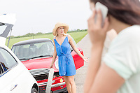 Angry woman standing by damaged cars with female using cell phone in foreground