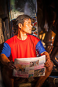 """03 DECEMBER 2012 - BANGKOK, THAILAND: A man reads a newspaper in the afternoon light on Th. Bamrung Muang in Bangkok. Thanon Bamrung Muang (Thanon is Thai for Road or Street) is Bangkok's """"Street of Many Buddhas."""" Like many ancient cities, Bangkok was once a city of artisan's neighborhoods and Bamrung Muang Road, near Bangkok's present day city hall, was once the street where all the country's Buddha statues were made. Now they made in factories on the edge of Bangkok, but Bamrung Muang Road is still where the statues are sold. Once an elephant trail, it was one of the first streets paved in Bangkok. It is the largest center of Buddhist supplies in Thailand. Not just statues but also monk's robes, candles, alms bowls, and pre-configured alms baskets are for sale along both sides of the street.      PHOTO BY JACK KURTZ"""